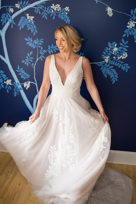 beautiful bride in stunning low cut wedding dress, wedding hair softly pulled back, on a handpainted blue wall in Oakleaf Cottage