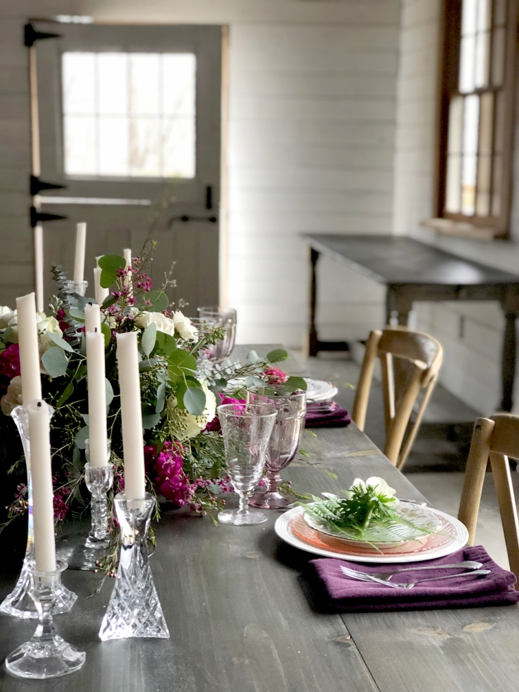 White barn wedding venue with tablesetting ideas for the head table. White and pretty deep pink flowers, mixed china and glassware.