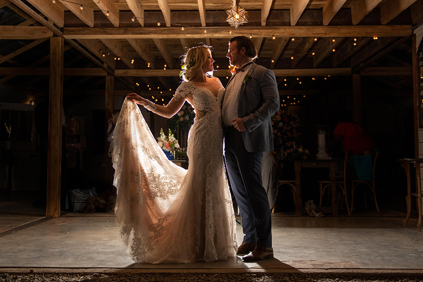 stunning wedding photo with light behind the couple, beautiful wedding dress glows from the light inside the venue