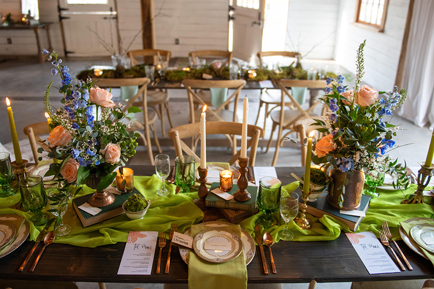 A spring green wedding table setting, with brass candlesticks, mismatched china, vintage books and stunning florals